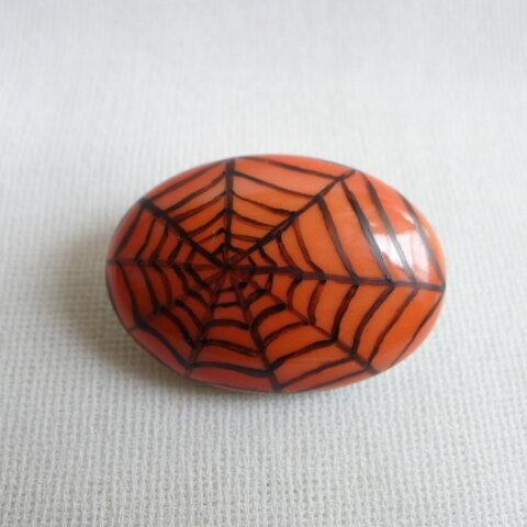 オレンジ釉薬に蜘蛛の巣模様のブローチ