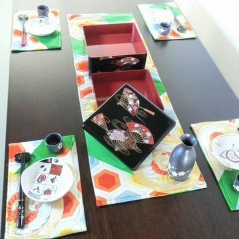 緑色にオレンジ色などの亀甲文様がはいったテーブルセンターとランチマット4枚のセット